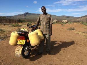 James hämtar vatten vid vår brunn till sig själv och andra i byn. Ibland har han 6 dunkar, dvs 120 liter på moppen!