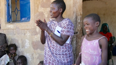 Jennifer tillsammans med Kapolong leder barnen i några körer innan maten delas ut.